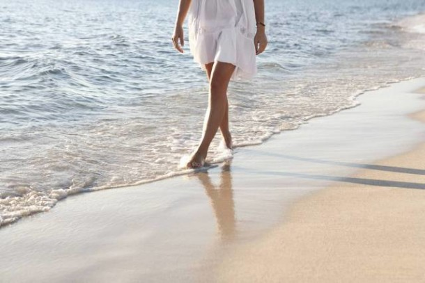 Woman's low section walking along shore